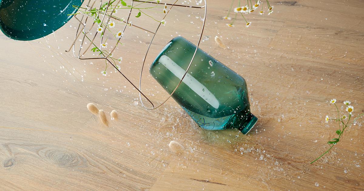 Glas dat valt op een BerryAlloc laminaatvloer wat is een slijtlaag